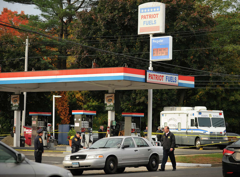 State and Milford police outside Patriot Fuels at 719 Boston Post Road in Milford, Conn. where a robbery suspect was shot and killed by a state police officer early Wednesday morning, October 23, 2013. Photo: Brian A. Pounds / Connecticut Post