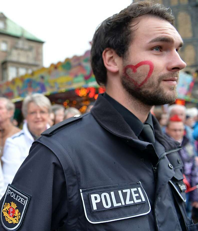 Have a heart, Officer: After allowing an admirer to draw on his face, a policeman watches a parade of acrobats and marching bands in Bremen, Germany. Photo: Carmen Jaspersen, AFP/Getty Images
