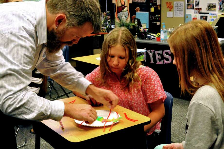 Dr. Montgomery, a visiting Biology professor from Truman State University, helps Nina Mitrofanova and Haley Burt divide their gummy cell. Photo: The Woodlands Preparatory School