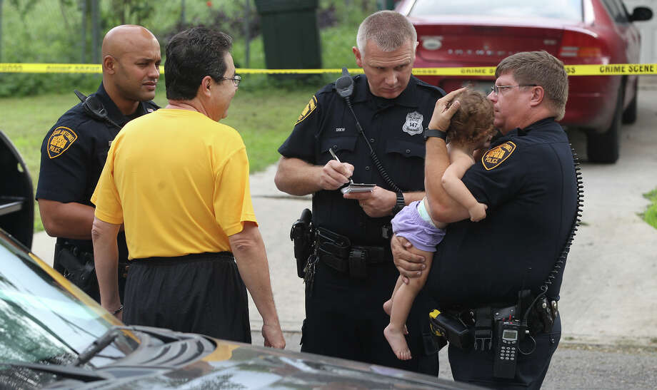 A San Antonio police officer holds a toddler in front of 9510 Moraga on the North Side after shooting took place around 9:00 a.m. . Investigators said the shooting appeared to be a suicide and that the victim appeared to be a woman in her early 20s. Photo: JOHN DAVENPORT, John Davenport / ©San Antonio Express-News/Photo may be sold to the public