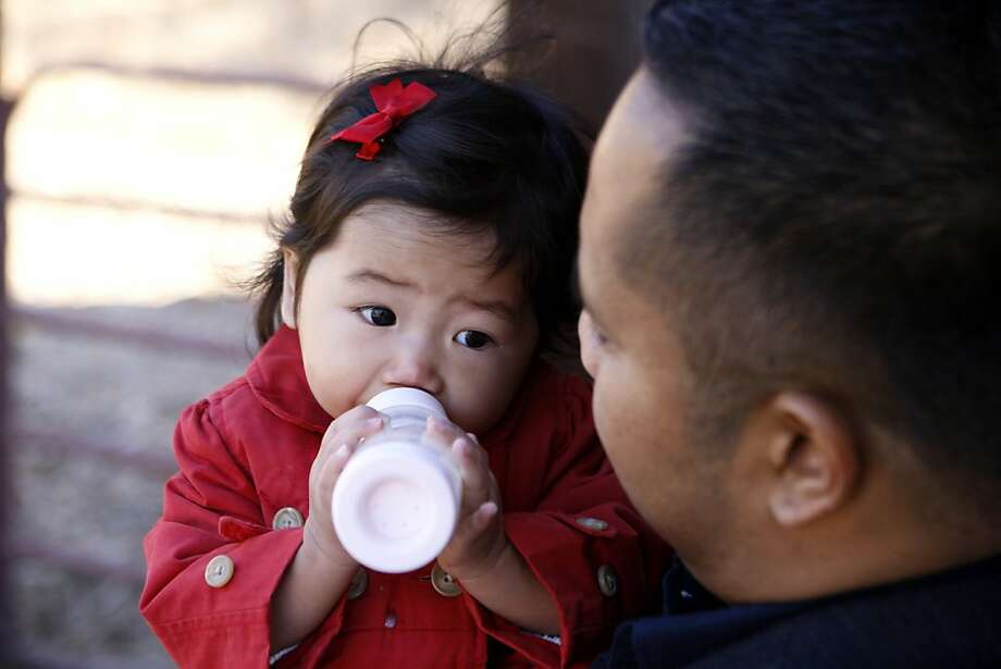 Karlo Agustin holds his daughter Leah while she drinks a bottle of mom Tammy Agustin's breast milk in Walnut Creek. Photo: Raphael Kluzniok, The Chronicle