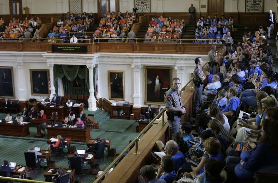 Texas state troopers keep watch as supporters and opponents of an abortion bill, mostly dressed in blue and orange to show their side, sit in the gallery of the Texas Senate chambers as lawmakers debate before the final vote, Friday, July 12, 2013, in Austin, Texas. The bill would require doctors to have admitting privileges at nearby hospitals, only allow abortions in surgical centers, dictate when abortion pills are taken and ban abortions after 20 weeks. (AP Photo/Eric Gay) Photo: Eric Gay, Associated Press