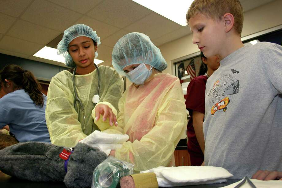 Ian Wietstruck, right, watches as his sister Abigail Wiestruck bandages the leg of a model dog under the guidance of Samantha Vela, a veterinary studies student at Carl Wunsche Senior High School. Photo: Provided By Carl Wunsche Senior High School