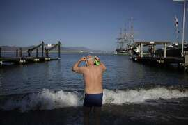 Dolphin Club  member Noel Turner of San Francisco  prepares for a swim as he enters the water at Aquatic Park on Monday, October 28, 2013 in San Francisco, Calif.