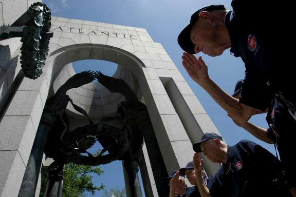 Houston-area World War II veterans in 2009 salute the granite pillar dedicated to Texas soldiers at the WWII Memorial in Washington D.C.