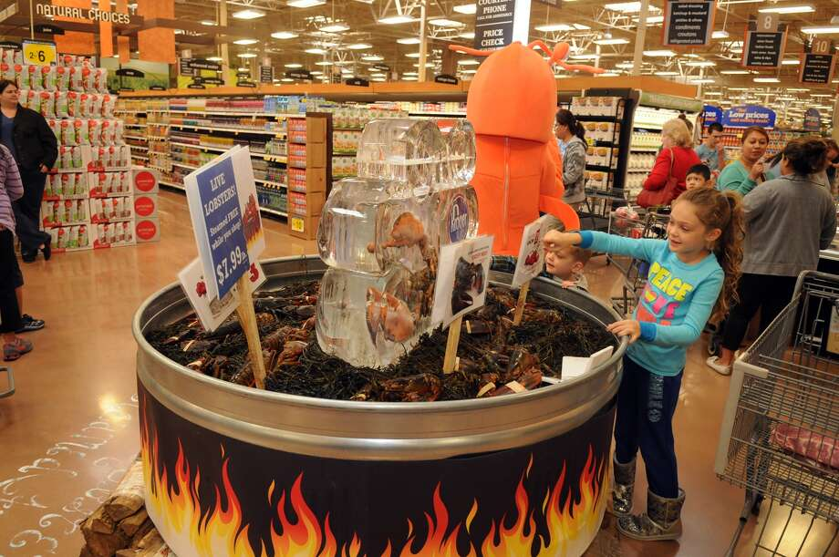 Brooke O'Brien, 7, from right, a 2nd grader at Kings Manor Elem., and her brother, Blake, 3, check out the lobster tank during the grand opening of the Kroger Marketplace in Kingwood. Photo: Jerry Baker, For The Chronicle