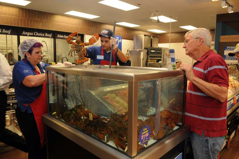 Deonna Ramos, from left, Seafood Captain, and Domingo Perez help customer Terry Neill, of Oakhurst, with his lobster selection during the grand opening of the Kroger Marketplace in Kingwood. Photo: Jerry Baker, For The Chronicle