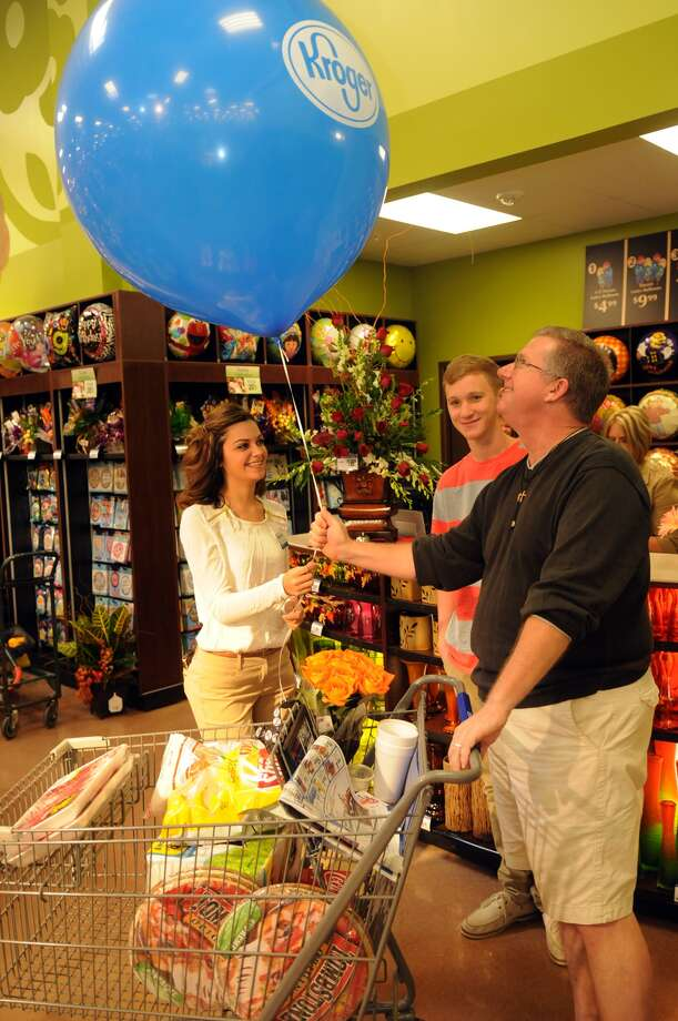 "Shayna Savoy, 23, left, delivers a ""hot air balloon"" to customer Roger Hill, of Kingwood, with his son Roger II, 16, a junior at Kingwood Park High School, during the grand opening of the Kroger Marketplace in Kingwood. Photo: Jerry Baker, For The Chronicle"