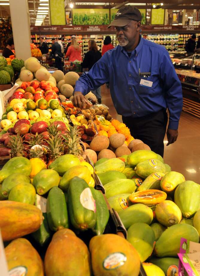 Samuel Bailey, of Baytown, spruces the exotic fruit section in the produce dept. during the grand opening of the Kroger Marketplace in Kingwood. Photo: Jerry Baker, For The Chronicle