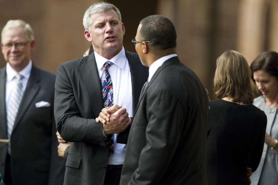 Titans head coach Mike Munchak, left, greets former Houston Oilers linebacker Al Smith, following the memorial service. Photo: Brett Coomer, Houston Chronicle