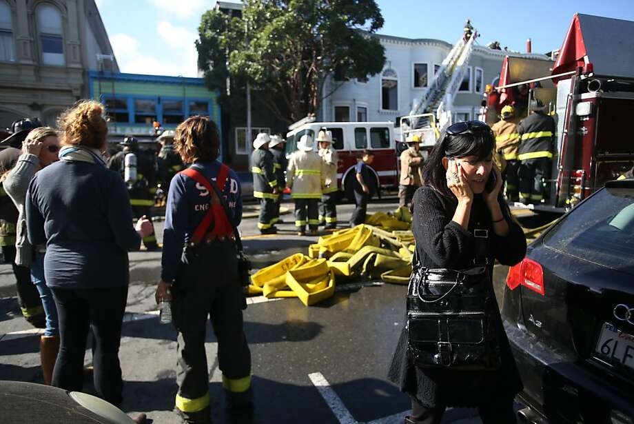 Nancy Myers, owner of a business affected by the three-alarm fire at 1448/1450 Valencia St. talks on her phone at the scene on Monday, Oct. 28, 2013. Photo: Mathew Sumner, Special To The Chronicle