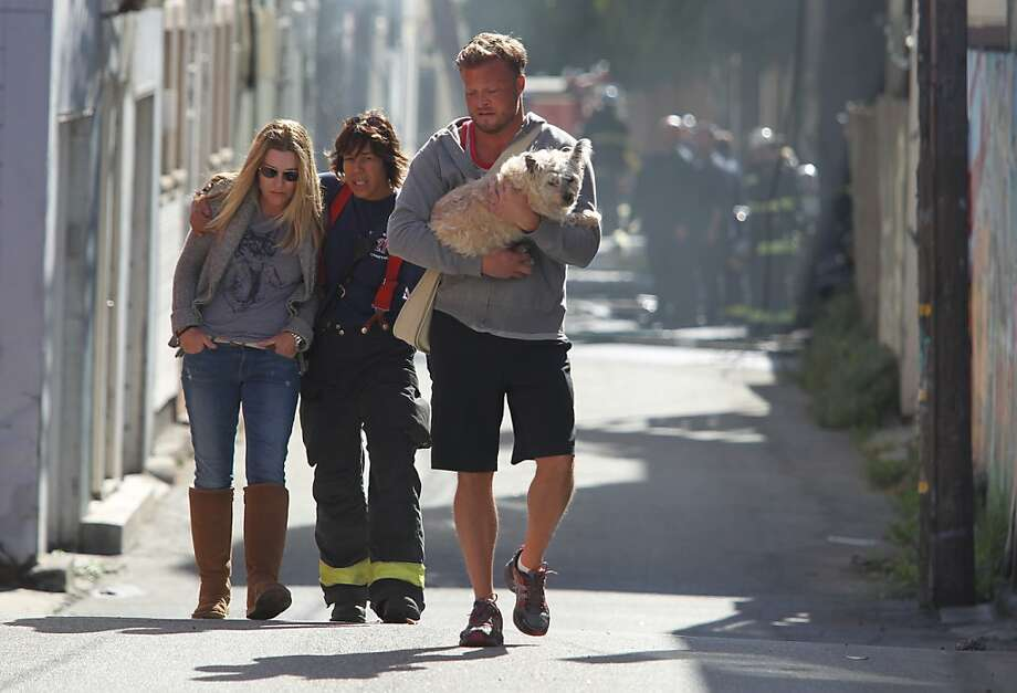 A firefighter helps the owners of one of four buildings at 26th and Poplar streets that were damaged by a midday fire Monday in S.F. No injuries were reported. Photo: Mathew Sumner, Special To The Chronicle