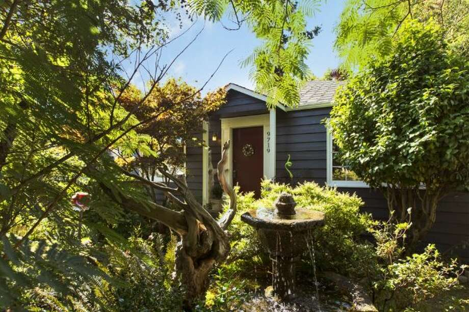 First comes 9719 3rd Ave. N.W. The 1,880-square-foot house, built in 1942, has three bedrooms, one bathroom, built-ins, an updated kitchen and bathroom, French doors, a deck, a greenhouse, a fire pit and a pond on a 6,700-square-foot lot. It's listed for $414,000. Photo: Courtesy Marshall Longtin,  Windermere Real Estate
