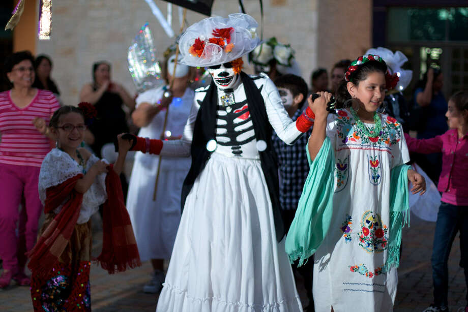 A dancer with URBAN-15's Carnaval de los Muertos twirls with young revelers at last year's event. This year, the troupe's first performance will be at El Rinconcito de Esperanza, 816 S. Colorado, at 6 p.m. Friday Photo: Steve Gilmore / Courtesy