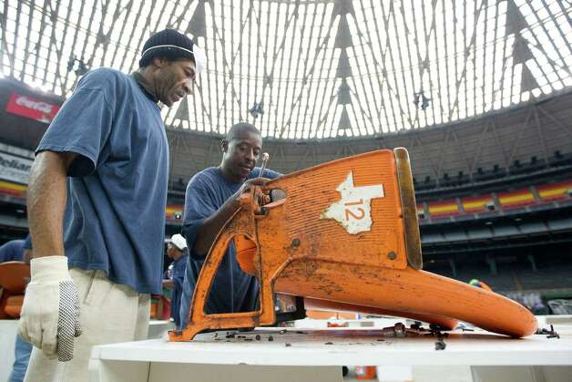 Kent Howard, left, and Cermase Garrett work on taking apart seats to be cleaned and adjusted as items are removed from the Astrodome, some of which will be sold or auctioned off Saturday. Photo: Johnny Hanson, Staff / Houston Chronicle