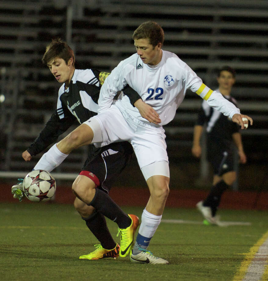 Pomperaug's Zachary Paulisin, 4, and Newtown's Matthew Mossbarger, 22, battle for the ball during the SWC boys soccer semifinals between Newtown High School and Pomperaug High School in Southbury, Conn, on Monday, October 28, 2013. Photo: H John Voorhees III / The News-Times Freelance