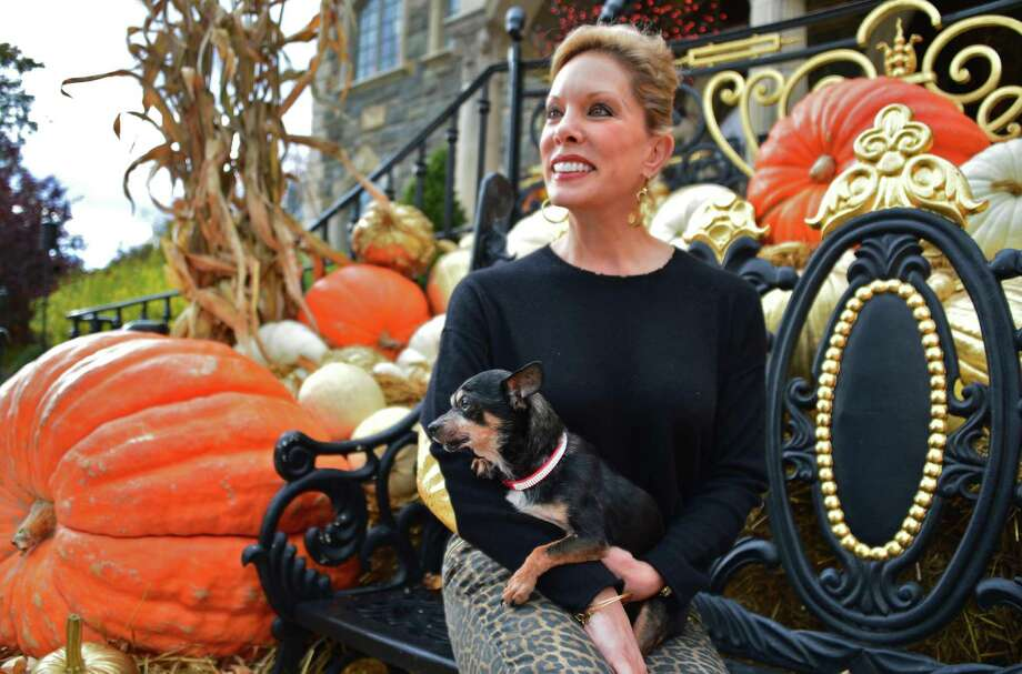 Michele Riggi with her latest rescued dog Rocky in front of her home's elaborate Halloween decorations Thursday Oct. 24, 2013, in Saratoga Springs. (John Carl D'Annibale / Times Union) Photo: John Carl D'Annibale / 00024355A