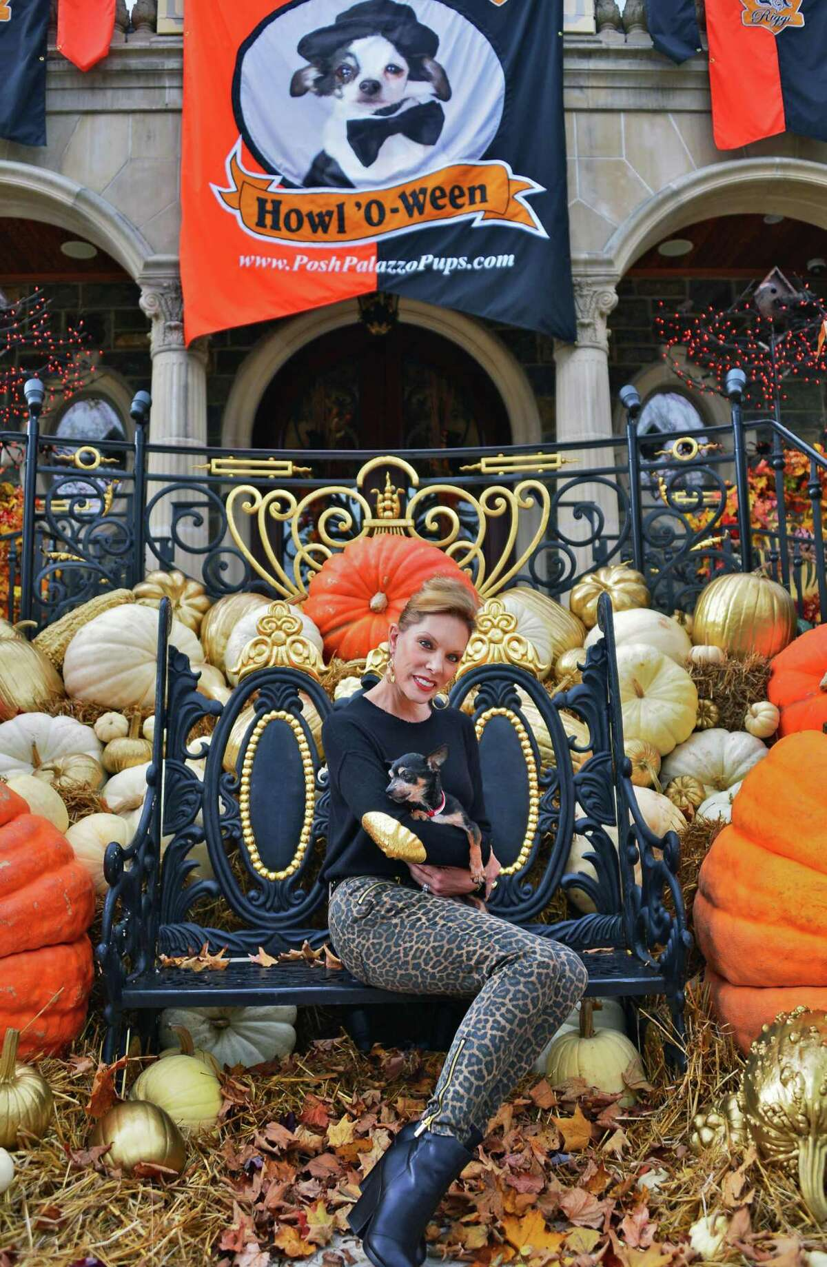 Michele Riggi with her latest rescued dog Rocky in front of her home's elaborate Halloween decorations Thursday Oct. 24, 2013, in Saratoga Springs. (John Carl D'Annibale / Times Union)