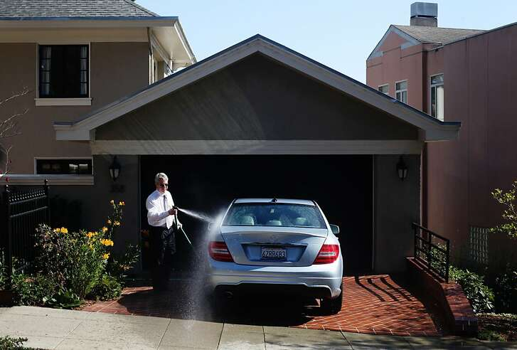 Tom Cooke washes his car on October 23, 2013 in the Forest Hill neighborhood of San Francisco, Calif. Mr. Cooke was washing his car after attending a wedding earlier in the day, and was headed to a funeral afterwards.