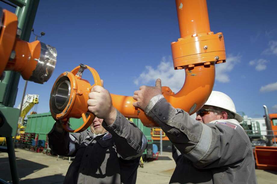 Green Field Energy Services employees adjust a pivoting gas line arm, used to fuel hydraulic fracturing units, during a test at Turbine Power Technology in Franklin, La., earlier this year. Photo: Brett Coomer / Houston Chronicle