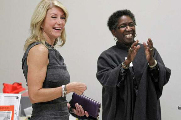 State Sen. Wendy Davis, left, visits Monday with lead clerk Melba Mackey and the staff at the Southside Community Center in east Fort Worth before she cast an early vote in Texas' Nov. 5 election.