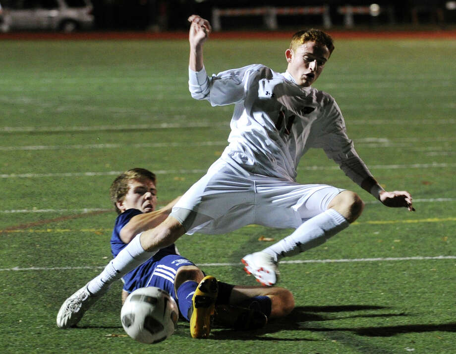 Greenwich's Patrick Santini is tripped up by Wilton defender Connor King during the first half of their FCIAC boys soccer semifinal matchup at Fairfield Ludlowe High School in Fairfield, Conn. on Monday, October 28, 2013. Photo: Brian A. Pounds / Connecticut Post