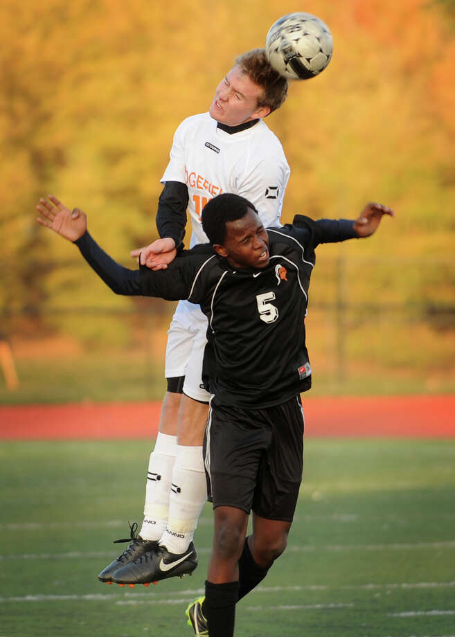 Ridgefield's Tyler Welton heads a ball over Stamford's Diallo Seydina in the first half of their FCIAC boys soccer semifinal game at Fairfield Ludlowe High School in Fairfield, Conn. on Monday, October 28, 2013. Ridgefield won the game 5-1. Photo: Brian A. Pounds / Connecticut Post