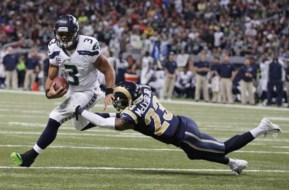 St. Louis Rams free safety Rodney McLeod (23) tackles as Seattle Seahawks quarterback Russell Wilson (3) as Wilson rushes toward the end zone during the first half of an NFL football game, Monday, Oct. 28, 2013, in St. Louis. (AP Photo/Tom Gannam) Photo: AP