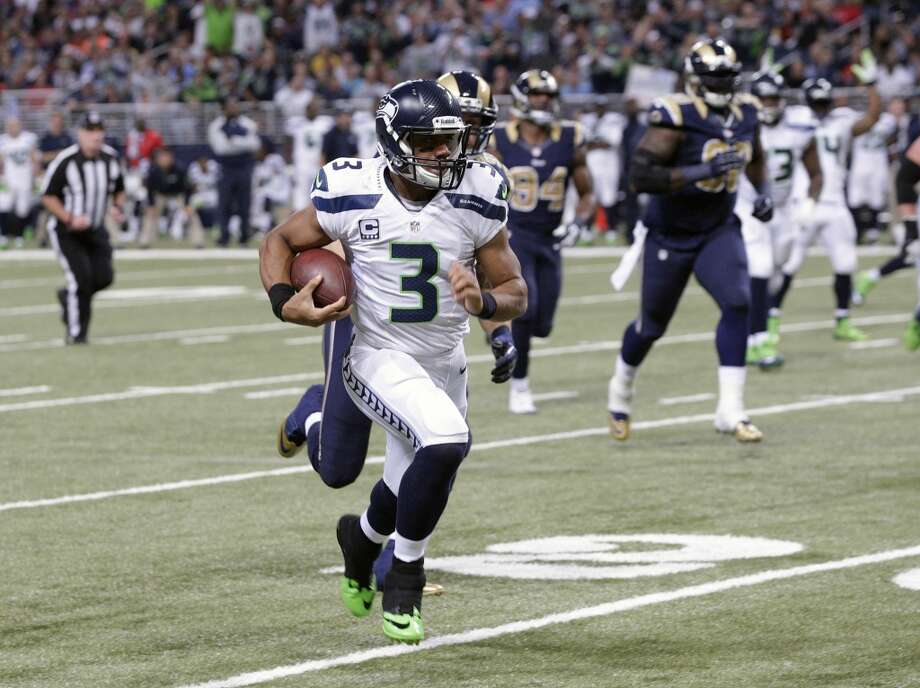 Seattle Seahawks quarterback Russell Wilson (3) rushes against St. Louis Rams defense during the first half of an NFL football game, Monday, Oct. 28, 2013, in St. Louis. (AP Photo/Tom Gannam) Photo: AP
