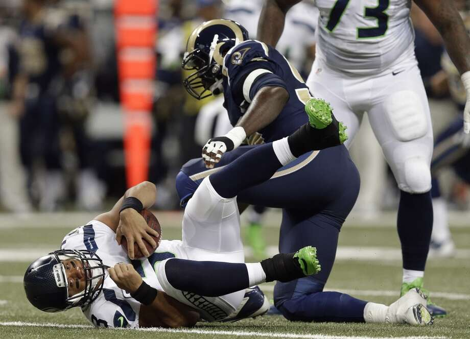 St. Louis Rams defensive end William Hayes (95) sacks Seattle Seahawks quarterback Russell Wilson (3) during the first half of an NFL football game, Monday, Oct. 28, 2013, in St. Louis. (AP Photo/Michael Conroy) Photo: AP