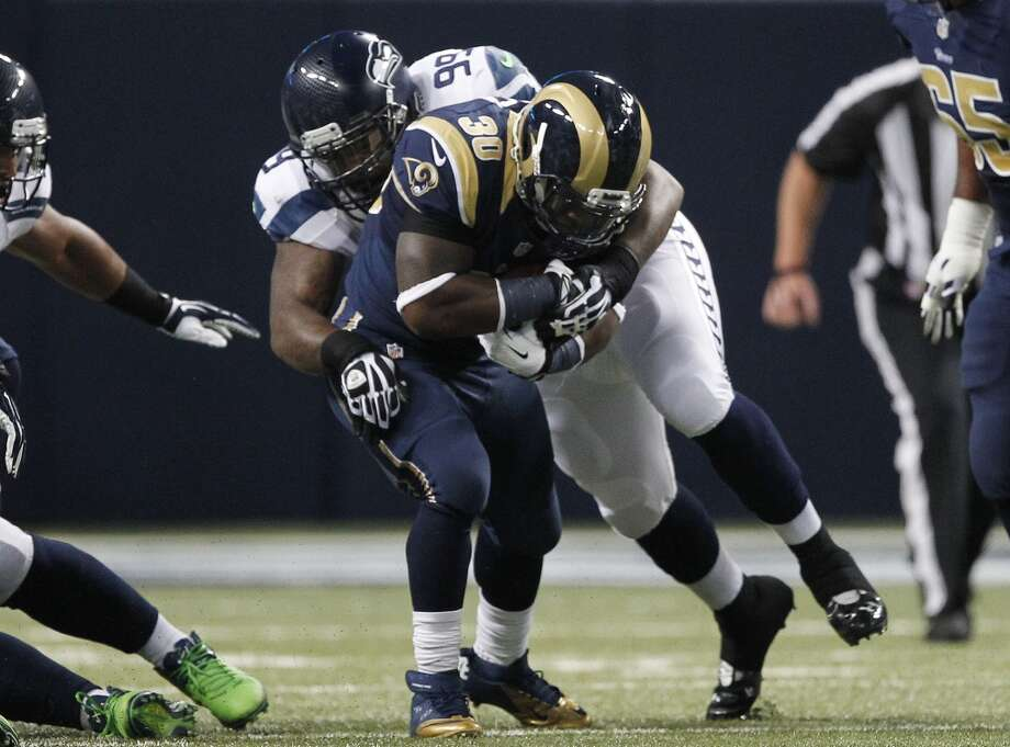 Seattle Seahawks defensive tackle Tony McDaniel (99) tackles St. Louis Rams running back Zac Stacy (30) during the first half of an NFL football game, Monday, Oct. 28, 2013, in St. Louis. (AP Photo/Kiichiro Sato) Photo: AP