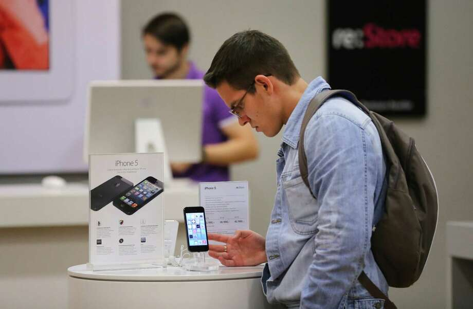 A customer inspects an iPhone 5 on display inside an Apple reseller store in Moscow earlier this month. Photo: Andrey Rudakov / Copyright 2013 Bloomberg Finance LP