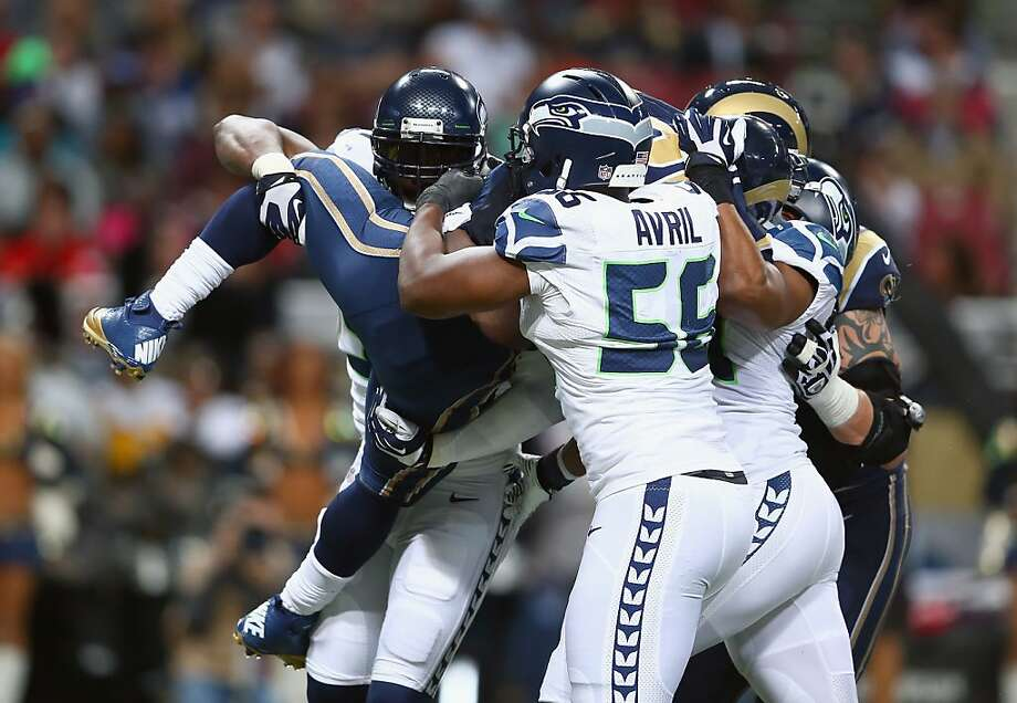 Cliff Avril and Seattle teammates lift and tackle the Rams' Zac Stacy, who ran for 134 yards - just 1 yard less than the Seahawks' total offense. Seattle still managed to win 14-9. Photo: Andy Lyons, Getty Images