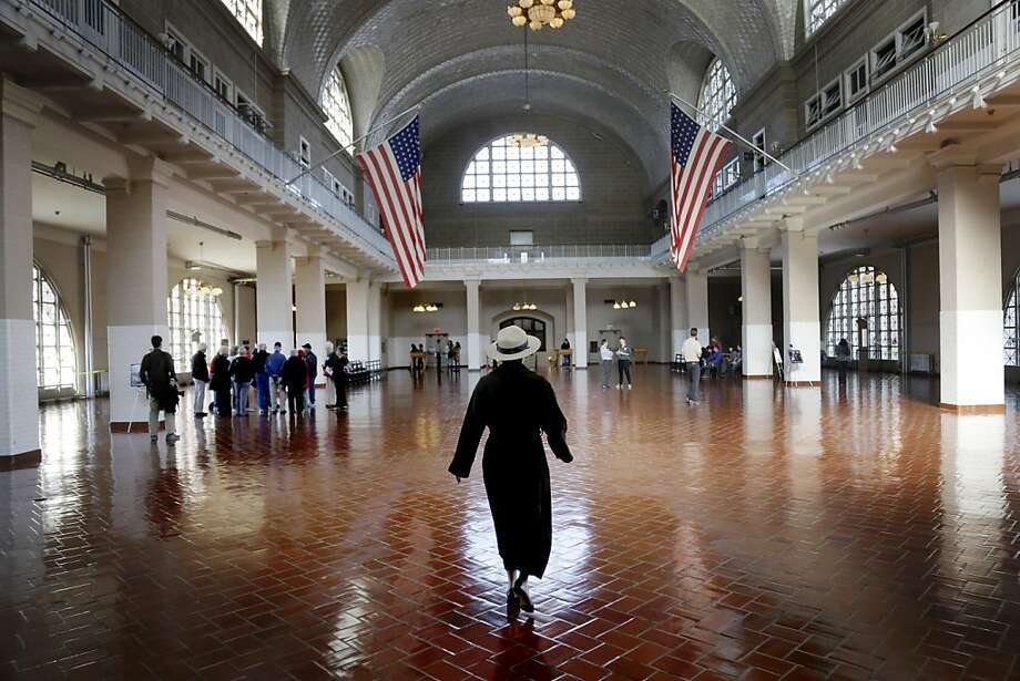 A park ranger walks through the registry room on Ellis Island in New York, Monday, Oct. 28, 2013. The island that ushered millions of immigrants into the United States received visitors Monday for the first time since Superstorm Sandy. Sandy swamped boilers and electrical systems and left the 27.5-acre island without power for months. (AP Photo/Seth Wenig) Photo: Seth Wenig, Associated Press
