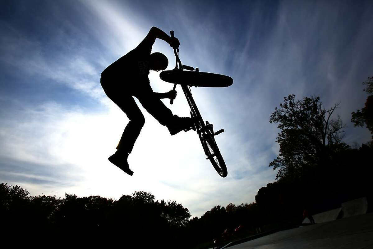 Christian Sass, 17, jumps a bike ramp at Kiwanis Park in St. Joseph, Mich. on a warm fall afternoon Monday Oct. 28, 2013. (AP Photo/The Herald-Palladium, Joe Rondone)