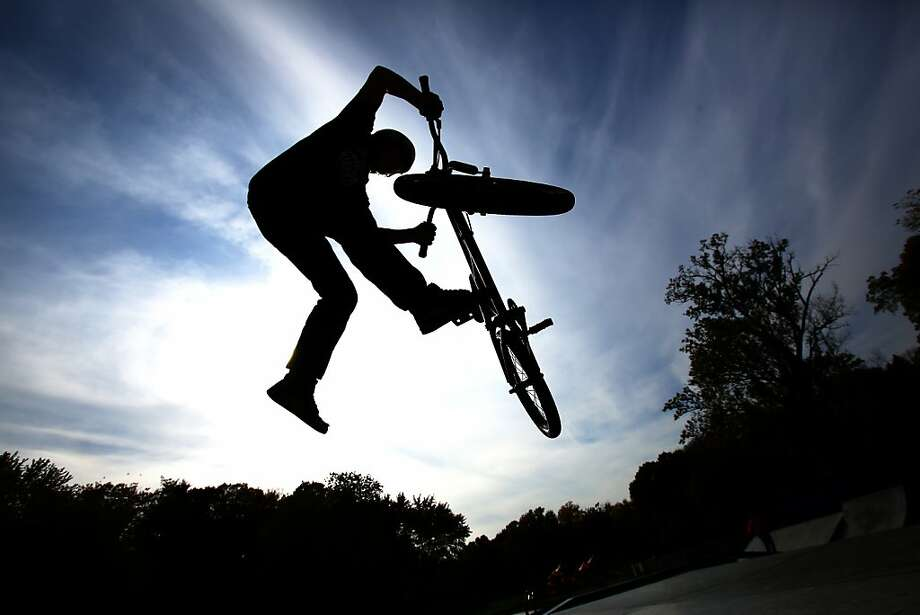 Christian Sass, 17, jumps a bike ramp at Kiwanis Park in St. Joseph, Mich. on a warm fall afternoon Monday Oct. 28, 2013.  (AP Photo/The Herald-Palladium, Joe Rondone) Photo: Joe Rondone, Associated Press