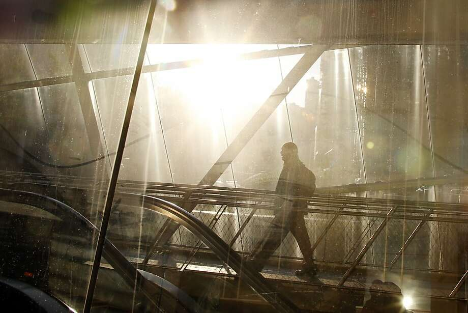The sun shines through the glass around the Gateway Center subway station as an evening commuter walks over a walkway on Monday, Oct. 28, 2013, in Pittsburgh. (AP Photo/Keith Srakocic) Photo: Keith Srakocic, Associated Press