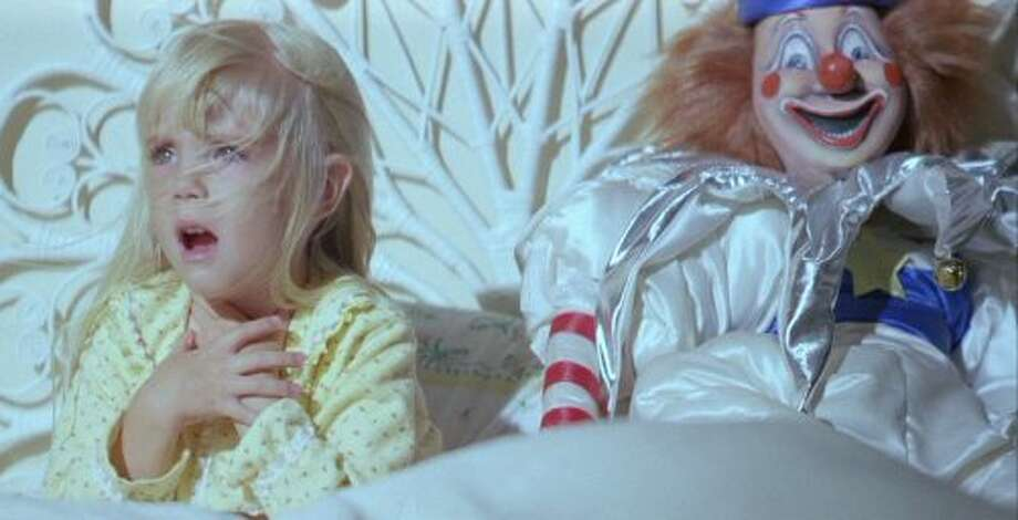 """Clowns:  While not the central evil force in the film, the gigantic, grinning clown doll in """"Poltergeist"""" (1982) is probably one of the most ill-conceived gifts a parent could give a child and is featured in some of the freakiest parts in the movie. Who can forget when Robbie checks under his bed and the life-sized doll wraps his arm around Robbie's neck and drags him under the bed. (Side note: apparently while filming that scene, the boy who played Robbie actually WAS suffocating and Steven Spielberg had to rush in to release him from the clown's clutches.) Photo: Handout, MGM"""