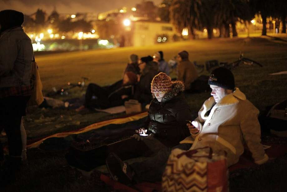 Protesters check their phones during a recent sleep-in at Dolores Park against the park-closure ordinance. Photo: Carlos Avila Gonzalez, The Chronicle
