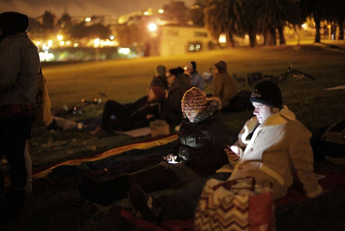 Jeremy Pollock and Cynthia Crews check their phones from their sleeping area at Dolores Park on Monday night, October 28, 2013 in San Francisco, Calif. The Harvey Milk LGBT Democratic Club hosted a sleep in to protest Supervisor Scott Wiener's proposed ordinance for city-wide park closure hours, which they believe targets the homeless and especially LGBT homeless youth.