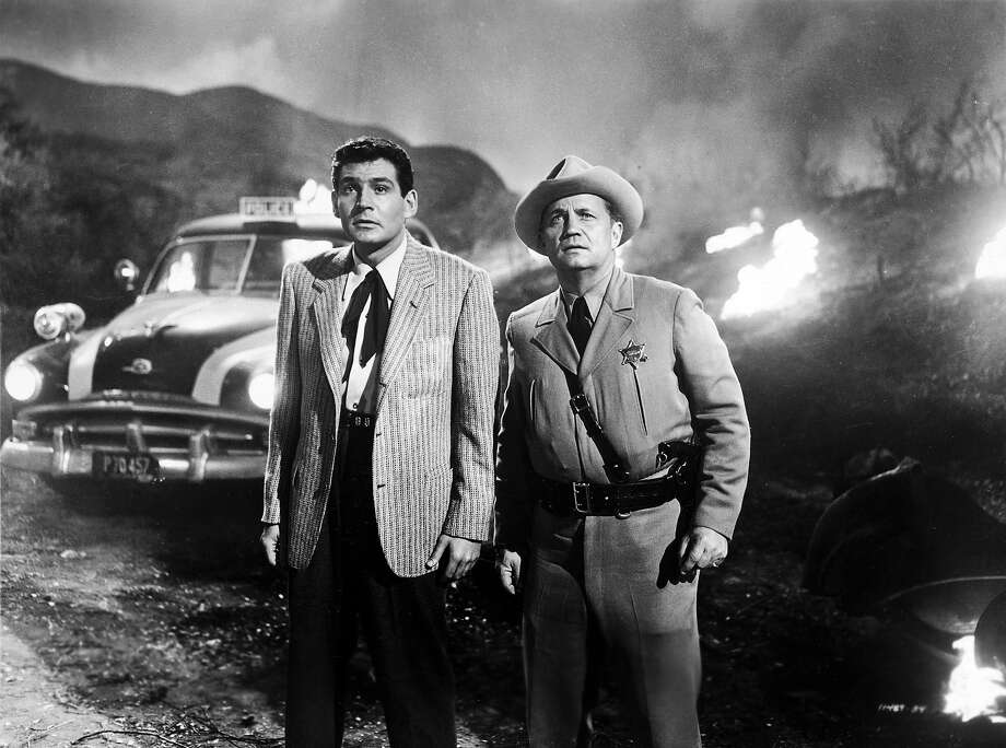 American actor Gene Barry and an unidentified man stand outdoors, looking in the distance with amazement in a still from the film, 'The War Of The Worlds,' directed by Byron Haskin, 1953. Photo: Paramount Pictures, Getty Images / Moviepix