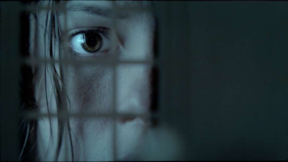 """Doll Houses:  Miniature models of haunted houses are never a good sign in horror movies. In """"The Awakening"""" (2011), Florence chases the ghost of a boy through a boarding school, ending up in an almost empty room with an exact replica dollhouse of the building in it. Peaking in through the tiny windows, she sees faceless dolls posed in scenes from the past few days – including her staring into the dollhouse at that moment ... and the ghost of the boy standing behind her. Photo: AP, Studio Canal UK"""