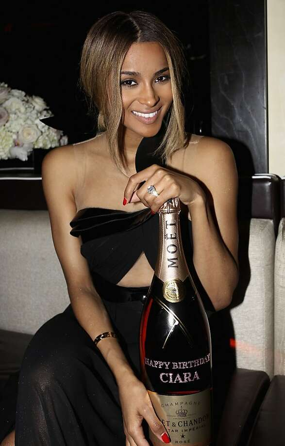 Enjoy passing out! R&B singer Ciara shows off an industrial-size bottle of Moet presented to her at The Hotel Derek in 