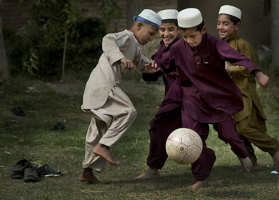 Having shed their sandals,Afghan schoolboys play football barefoot during recess in Kandahar. Afghanistan has gone soccer crazy after the national team beat India to win the South Asian Federation Football Cup earlier this month. Photo: Anja Niedringhaus, Associated Press