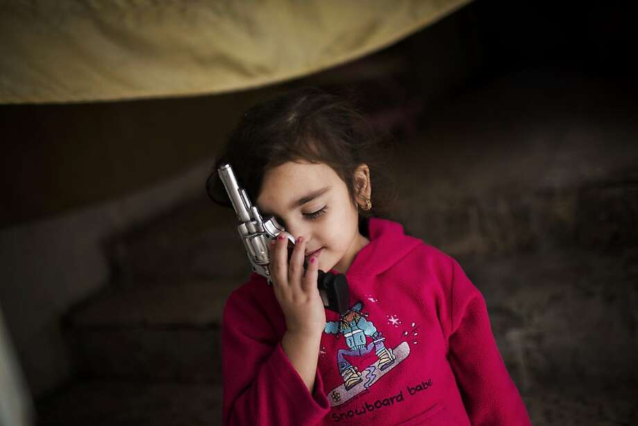 Armed 'snowboard babe':A Syrian refugee girl plays with a realistic toy gun at her family's house in Zarqa, Jordan. More than 420,000 Syrian refugees have settled in Jordan's cities, struggling for survival on U.N. foods stamps and straining the country's resources. Photo: Manu Brabo, Associated Press