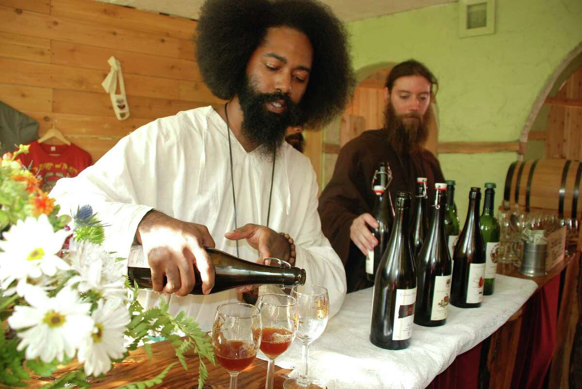 Enchanted Manor Meadery owner Jon Odom, right and employee Antoine Culbreath pour mead at the Texas Renaissance Festival. The honey-based wine is the official mead of the Texas Renaissance Festival.