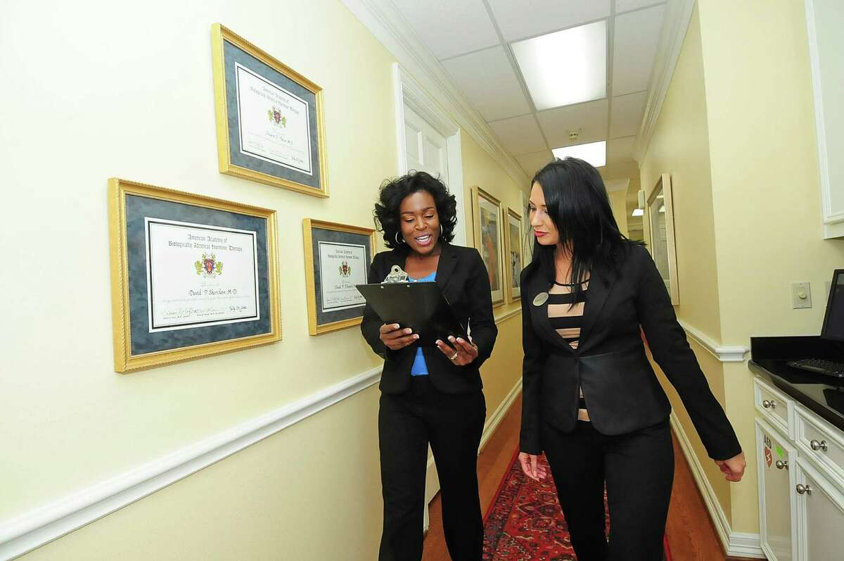 Andrea Johnson of the nursing department, left, and Erica Torres-Dudziak, recruitment director, take care of business at Hotze Health & Wellness Center in Katy. Hotze ranked No. 3 on the small-company list of top employers.