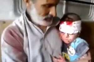 In this image taken from video obtained from the Shaam News Network, which has been authenticated based on its contents and other AP reporting, a Syrian man comforts a child injured by a missile strike in Raqqa, Syria, Wednesday, Aug. 7, 2013. Wednesday's missile attack came after Human Rights Watch said missiles fired by the Syrian army into populated areas have killed hundreds of civilians in recent months. (AP Photo/Shaam News Network via AP video)