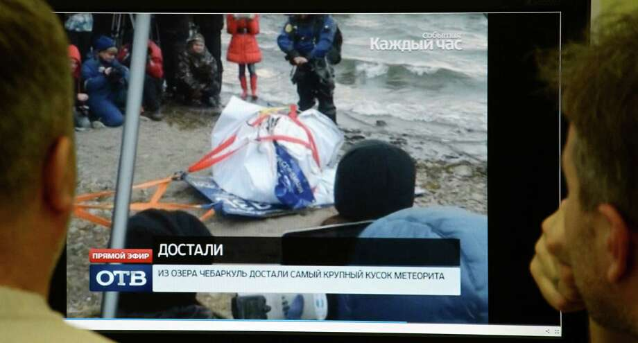 Men look in Moscow on October 16, 2013, at a computer screen displaying a team of divers pulling out a 1.5-metre-long (five-foot-long) suspected meteorite wrapped  it in a special casing from the lake Chebarkul  in the Chelyabinsk region. Russian divers pulled today from a murky lake in the Urals a half-tonne suspected meteorite said to have been part of a meteor whose ground-shaking shockwave hurt 1,200 people in February. AFP PHOTO / STR Photo: -, Getty Images / 2013 AFP