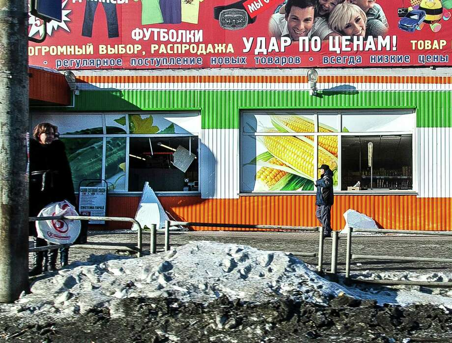 People stand in front of the facade of a local shop which was damaged by a shockwave from a meteor in the Urals city of Chelyabinsk, on February 15, 2013. A meteor strike in central Russia that left today hundreds of people injured is the biggest known human toll from a space rock, a British expert said. AFP PHOTO / 74.RU/ OLEG KARGOPOLOV